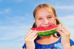 Young girl biting into a slice of watermelon.